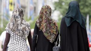 Drei junge Frauen mit Kopftüchern gehen durch die Innenstadt von München, Foto: dpa/picture-alliance