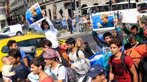 Flüchtlinge in Ungarn halten Merkel-Plakate; Foto: Reuters/B. Szabo