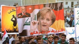 Demonstranten in Bagdad halten ein Bild von Merkel. Foto: Hella Mewis
