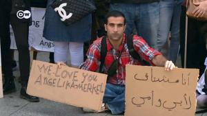 Ein syrischer Flüchtling in Berlin mit Angela-Merkel-Schild; Foto: S.Amri/DW