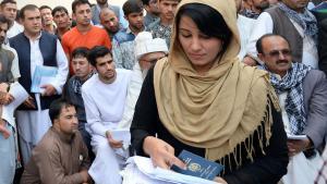 Eine Afghanin hält ihren neuen Reisepass in den Händen an der Passstelle in Kabul; Foto: picture-alliance/dpa/S. Bandari