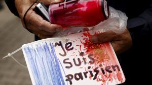 """Trauernder hält Plakat mit Aufschrift """"Je suis Parisien""""; Foto: Reuters/K. Pempel"""