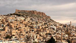 """Multiethnischer Grenzort: Die Stadt Mardin liegt am Tur Abdin, dem """"Berg der Knechte"""" - tief im Südosten der Türkei und ganz nah an der syrischen Grenze. In der Stadt mischen sich seit Jahrhunderten verschiedene Kulturen und Religionen. Muslime wohnen Tür an Tür mit Christen. Neben Türkisch sprechen die Menschen hier Arabisch, Aramäisch und Kurdisch. Diese Vielfalt hat Mardin bekannt gemacht, auch außerhalb der Türkei."""