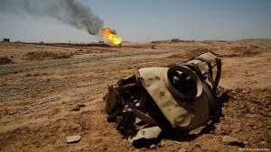 Zerstörtes militärisches Fahrzeug vor brennenden Ölquellen; Foto: picture-alliance/dpa