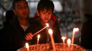 Ein Junge entzündet in der Geburtskirche in Bethlehem eine Kerze (Foto: dpa)