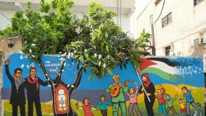 """Wandbild zeigt Juliano Mer Khamis vom """"Freedom Theatre"""" und Safdar Hashmi von der """"Jana Natya Manch""""-Straßentheater-Company neben einer Handala-Figur im Innenhof des """"Freedom Theatre"""" im Flüchtlingslager Jenin; Quelle: Freedom Theatre"""