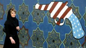 Iranische Frau läuft an einem Graffiti vorbei, welches eine Pistole in den Farben der amerikanischen Flagge darstellt