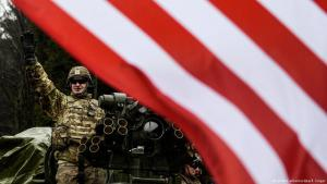 US-Soldat auf einem Panzerfahrzeug hinter amerikanischer Flagge; Foto: picture-alliance/dpa/F. Singer
