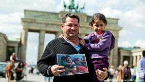 Der irakische Flüchtling Laith Majid Al-Amirij mit seiner Tochter Noor vor dem Brandenburger Tor; Foto: picture-alliance/dpa/J. Carstensen
