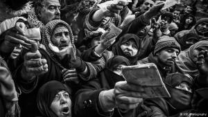 """Menschen in Not: Im Januar 2013 reiste Yusuke Suzuki über die türkische Grenze ins syrische Aleppo ein. Dies ist eine Aufnahme seiner Serie """"City of Chaos"""". """"Laut schrien die Menschen beim Verteilen von Decken. Kaum einer hatte genug Gas zum Heizen und der Winter war extrem kalt"""", berichtete Yusuke Suzuki."""