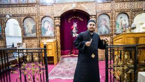 Priester Vater Filtawos steht vor dem Altar seiner Kirche in Ezbeth Raflah; Foto: Flemming Weiß-Andersen