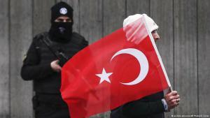Mann mit türkischer Nationalfahne passiert Polizist vor Absperrung in Istanbul; Foto: picture-alliance/AP/E. Gurel