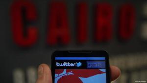 Smartphone mit Twitter-Logo vor Hintergrund mit der Aufschrift Kairo