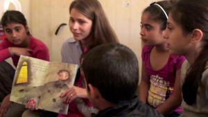 Die Kinderbuchautorin Nadine Kaadan liest für eine Gruppe von englischen und syrischen Kindern; Quelle: privat