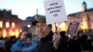 """Ein Mann hält ein Plakat mit dem Schriftzug """"Hate will not divide us"""" am Trafalgar Square in Gedenken an die Opfer des Anschlags in London vom 22.3.2017; Foto: Getty Images/J. Taylor"""