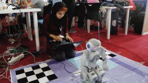Eine iranische Studentin setzt einen Roboter während des International Iran Open Robocup 2016 in Bewegung; Foto: picture-alliance/dpa