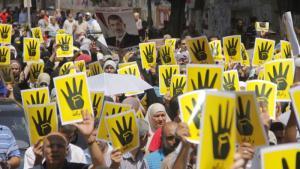 """Anhänger der Muslimbruderschaft zeigen das """"R4bia""""-Symbol als Zeichen ihrer Solidarität mit dem zerstörten und als Rābiʿa bekannt gewordenen Protest-Sit-in im August 2013; Foto: wikipedia"""