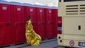 Flüchtlingsalltag: Eine Momentaufnahme, malerisch, trotz des Flüchtlingselends drumherum. Aufgenommen hat Herlinde Koelbl dieses Bild auf Sizilien. Tausende Geflüchtete aus Afrika waren bereits versorgt, viele ruhten sich auf den Pritschen eines notdürftigen Erstaufnahmelagers aus, andere warteten in den Bussen. Der Presserummel war längst vorbei, als dieser Mann zu den Dixi-Klos eilte. Koelbl stand zufällig da.