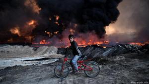 Irakischer Junge passiert mit seinem Fahrrad brennendes Ölfeld in Qayyarah bei Mossul, das vom IS bombardiert wurde; Foto: Getty Images/C. Court