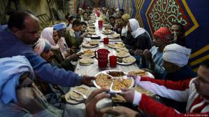 """In muslimisch geprägten Ländern werden im Ramadan kostenlose Mahlzeiten an Bedürftige ausgeteilt. Das Geben von Almosen bildet eine der """"fünf Säulen des Islam"""" - neben dem Glaubensbekenntnis, dem täglichen Gebet, der Pilgerfahrt nach Mekka und dem Fasten. Die Gläubigen verzichten von Sonnenaufgang bis Sonnenuntergang auf Nahrung und Getränke. Am Abend treffen sich viele in Moscheen, auf öffentlichen Plätzen oder in Festzelten, wie auf diesem Bild in Kairo, um das Fastenbrechen, den """"Iftar"""" zu feiern."""