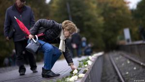 Frau legt Blumen in Gedenken an die Opfer des Holocaust an Gleis 17 des Berliner Bahnhofs Grunewald nieder; Foto: imago/IPON