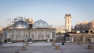 Ein Schüler der Jamiah Darul Uloom telefoniert auf dem Dach des Rohbaus der Makki Moschee. Im Hintergrund ist eines der Minarette zu sehen, welches die Regierung kürzen liess; Foto: Philipp Breu