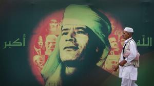 """Ein Libyer aus Tripolis passiert im Jahr 2009 Plaktwand mit dem Konterfei Gaddafis und dem arabischen Schriftzug """"Gott ist groß""""; Quelle: AP/Ben Curtis"""