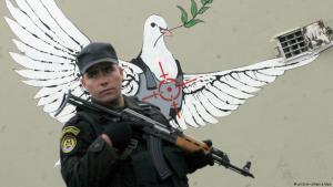 Bewaffneter palästinensischer Soldat vor einem Banksy-Graffiti in Bethlehem, West Bank; Foto: picture-alliance/dpa