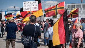 Teilnehmer rechtsextremer Organisationen demonstrieren gegen Muslime und Angela Merkels Flüchtlingspolitik am Berliner Hauptbahnhof; Foto: picture-alliance/dpa