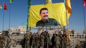 """Einheiten der """"Syrian Democratic Forces"""" vor einem Poster Öcalans nach der Einnahme Rakkas am 19. Oktober 2017; Foto: AFP/Getty Images"""