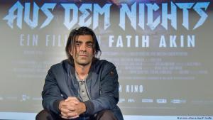 """Der Regisseur Fatih Akin vor Kino-Plakat """"Aus dem Nichts""""; Foto: dpa/picture-alliance"""