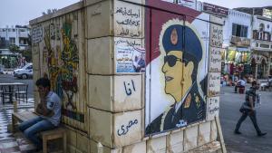 Ein Mann sitzt neben einem Wandgemälde Abdel Fattah al-Sisis in Sharm al-Sheikh; Foto: Khaled Desouki/AFP/Getty Images