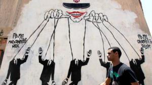 """Symbolbild """"In den Fängen der Autokratie"""" - Graffiti in Kairo zeigt das ägyptische Militär als Strippenzieher; Foto: Nasser Nasser/AP"""
