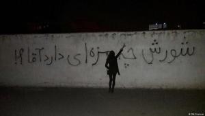 """Iranerin vor Graffiti mit der Aufschrift: """"Wie schmeckt Ihnen die Revolte, Herr?!"""" (Als """"Herr"""" wird im Iran auch Ajatollah Khamenei bezeichnet); Foto: DW"""