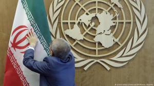 Ein Mitarbeiter der Vereinten Nationen platziert in New York die Fahne des Iran neben dem UN-Symbol; Foto: picture-alliance/newscom