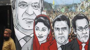 Ein Anhänger der PML-N steht neben Porträts der Familie des früheren, dreifachen Ministerpräsidenten Nawaz Sharif und seiner Familie im pakistanischen Karatschi; Foto: EPA/Shahzaib Akber