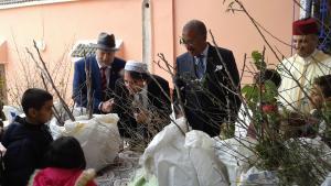 """Der US-Botschafter Marokkos, Dwight Bush Sr., verteilt gemeinsam mit  dem marokkanischen Provinzgouverneur Younes Elbathaoui, dem Vorsitzenden der """"Jüdischen Gemeinde von Marrakesch-Safi"""", Jacky Kadoch, und dem Vorsitzenden der """"Stiftung Hoher Atlas"""" , Yossef Ben-Meir, Obstbäume an Landwirte und ihre Kinder im Jahr 2016; Foto: High Atlas Foundation"""