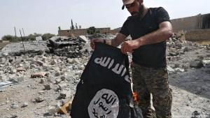 Anhänger einer Miliz in Syrien verbrennt eine Fahne des IS in Rakka; Foto: picture-alliance/AP/dpa