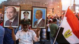 Ein Mann hält während einer Kundgebung auf dem Tahrirplatz in Kairo am 3. Juni 2014 Bilder des ägyptischen Präsidenten Abdel Fattah al-Sisi und des früheren Präsidenten Gamal Abdel Nasser; Foto: Reuters/Asmaa Waguih