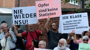 Teilnehmer einer Schweigeminute erinnern mit Plakaten auf der Kölner Keupstraße an den 15. Jahrestag NSU-Nagelbombenanschlag, bei dem dort 22 Menschen verletzt wurden, vier davon schwer; Foto: Roberto Pfeil/dpa