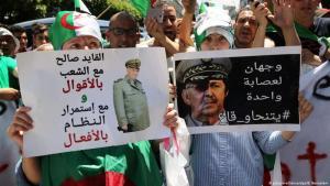 """Demonstranten in Algier halten Plakate mit der Aufschrift hoch: """"Gaid Saleh - zwei Gesichter des gleichen Regimes - alle müssen verschwinden!""""; Quelle: picture-alliance/dpa/B.Bensalem"""