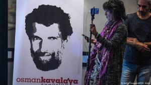 Journalisten vor einem Plakat des inhaftierten Intellektuellen Osman Kavala ein Jahr nach seiner Festnahme in der Türkei; Foto: Getty Images/AFP/O. Kose