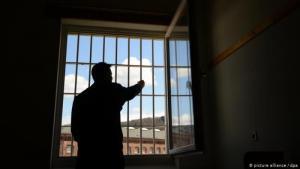 Häftling in einer Gefängniszelle von hinten an einem Fenster stehend; Foto: picture alliance/dpa