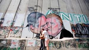 Ein Paar vor einem Abschnitt der Mauer in Jerusalem, auf dem als Wandmalerei Donald Trump and Benjamin Netanjahu zu erkennen sind; Foto: Getty Images/AFP/M.A. Shaers