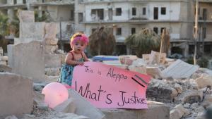 """Sama steht 2016 auf einer Ruine in Aleppo: Sie hält ein Plakat mit der Aufschrift: """"Das ist Aleppo. Was ist Gerechtigkeit?""""; Quelle: """"For Sama""""/Waad al-Kateab"""