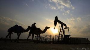 Kamele an einer Erdölförderanlage in der Wüste; Foto: picture-alliance/AP/H. Jamali