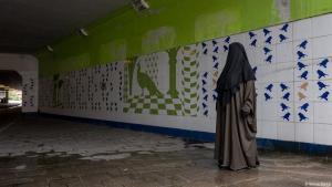 Eine Frau in einem leeren Tunnel in Amsterdam trägt eine schwarze Burka; Foto: Sanne Derks