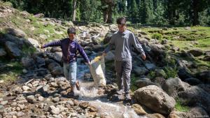 Majid Magray (12) und Waseem Ahmed (16) bei Aufräumarbeiten. Hier tragen sie den Müll von einem Wasserfall weg; Foto: Furkan Khan