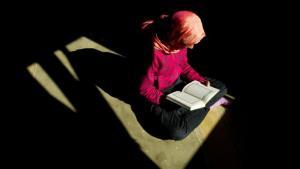 Eine Muslima liest den Koran in Dresden; Foto: picture-alliance/dpa