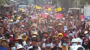 Demonstranten tragen Plakate und zeigen ein dreifingriges Zeichen des Widerstands auf einer Hauptstraße während einer Demonstration in Mandalay, Myanmar am 8.03. 2021. Foto: AP Photo